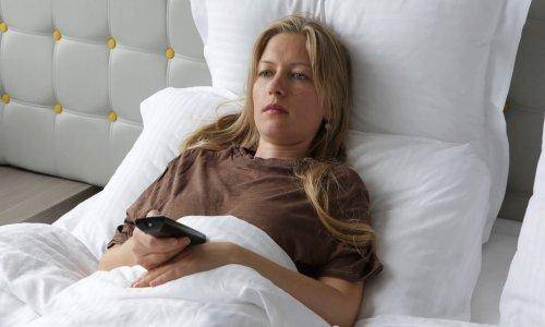 woman lying in bed watching tv
