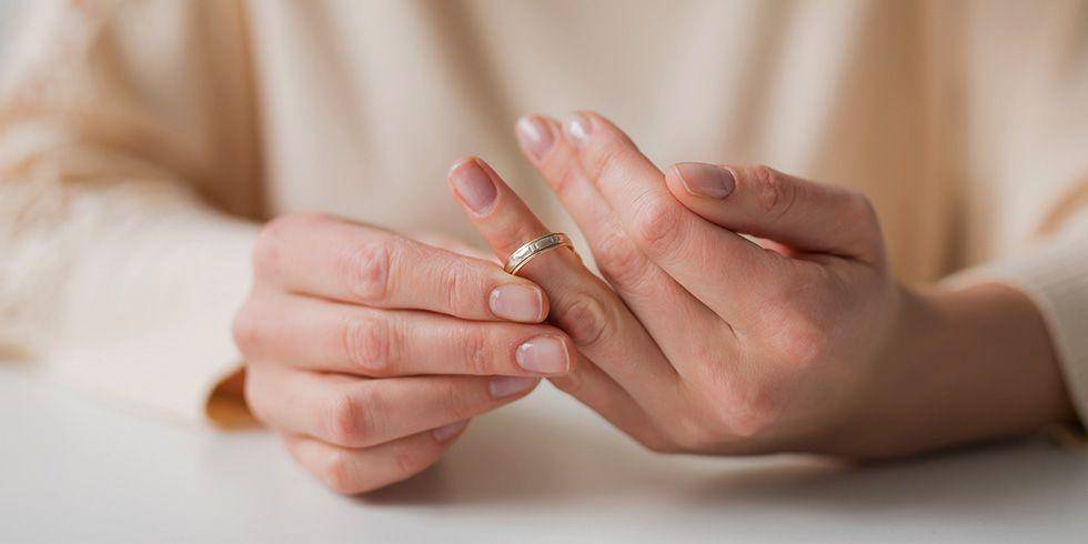 woman removing ring from finger
