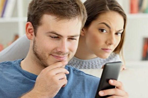 woman stalking man with phone