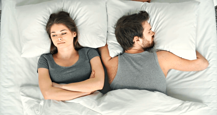 worried woman in bed with husband