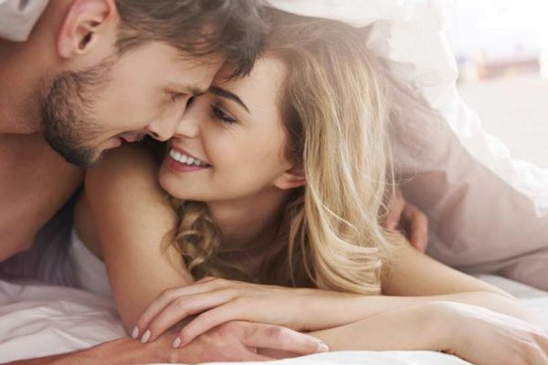 man and woman smiling in bed