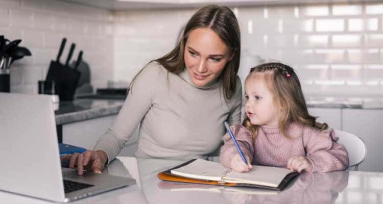 Young mother helping daughter with her homework table dining room