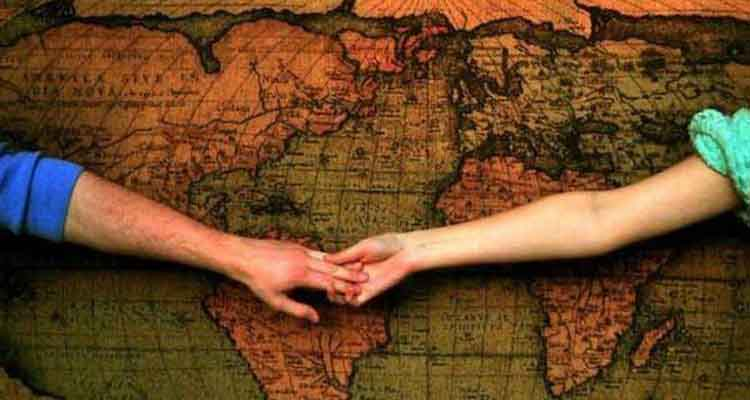 Couple holding hand with a globe in background