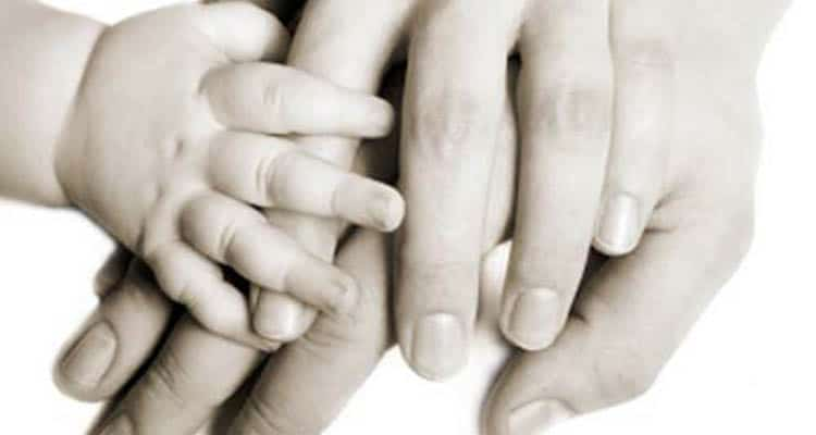Newborn's hand with their parents