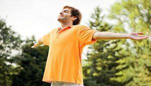 man outdoors, arms wide open