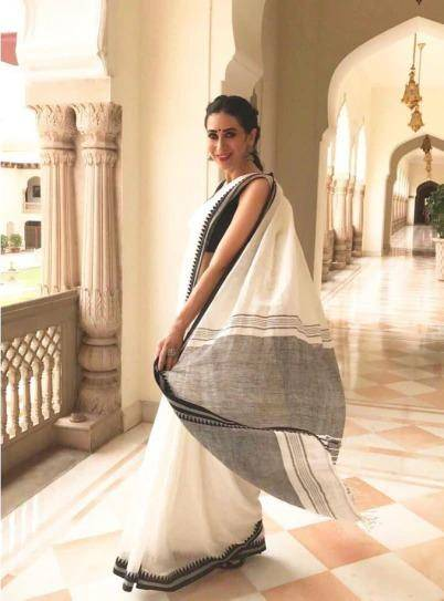 Karisma Kapoor in white-and-black cotton saree, with a pair of sliver jhumkas and bindi bloomed like summer rose