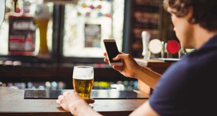 Man texting with glass of beer