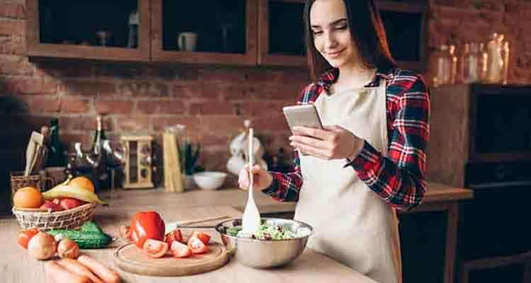 Girl looking on phone while cooking