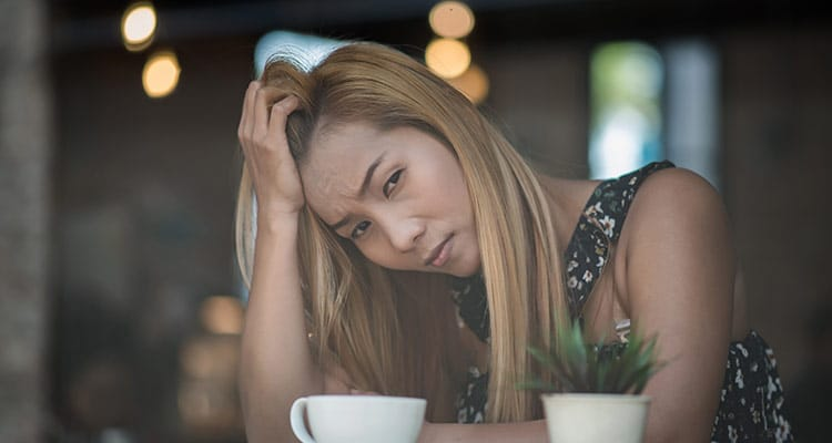 sad young woman sitting cafe