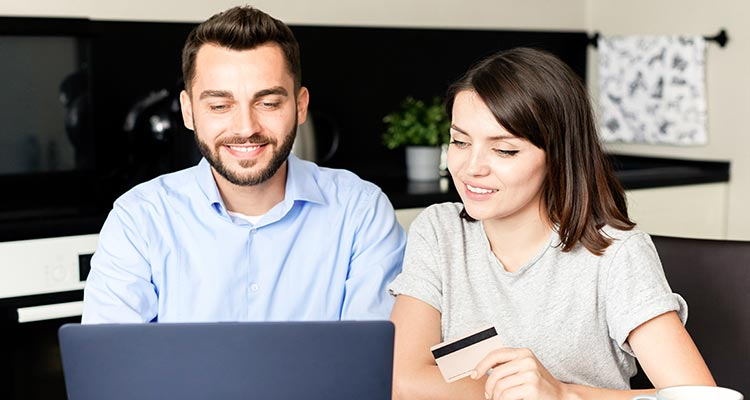 miling young couple sitting kitchen table using laptop while paying bills