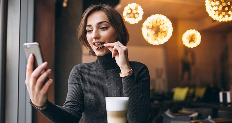 Woman chatting on the phone and drinking coffee in a cafe