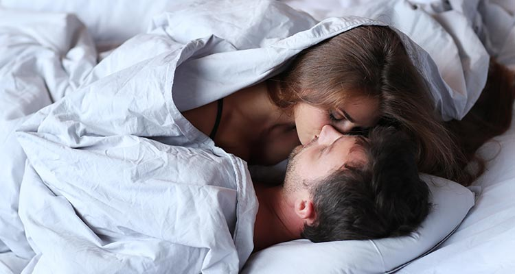 young passionate couple kissing on bed