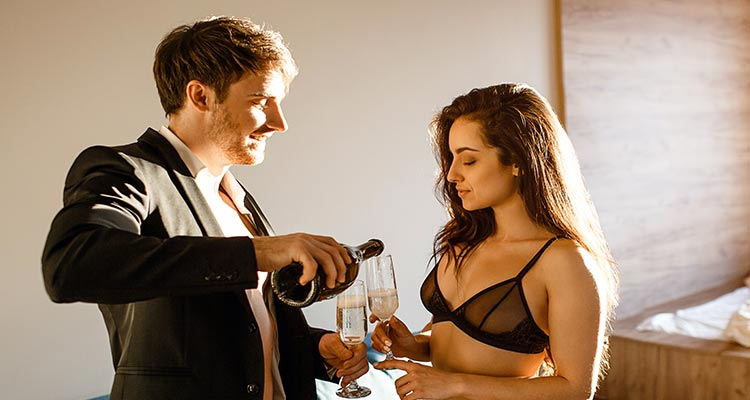 Sexy couple pouring-sparkled wine