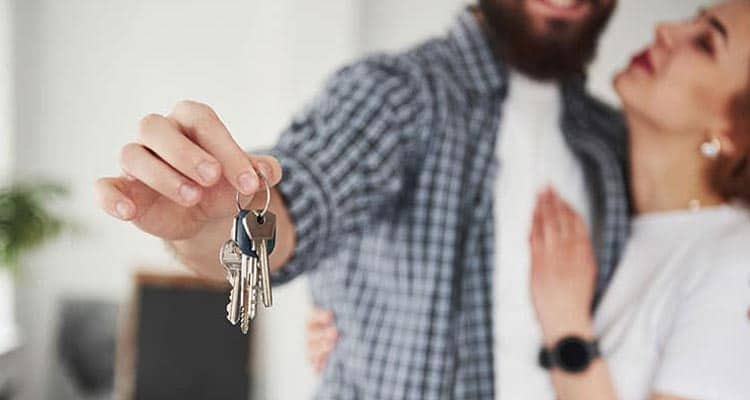 Couple hugging and holding house key