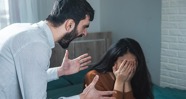 Aggressive man abusing woman in room