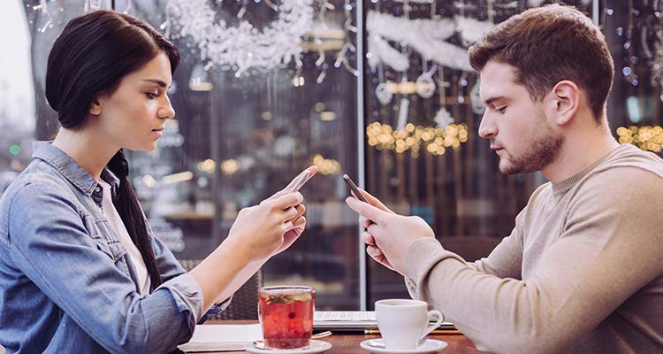 Couple ignoring each other in café