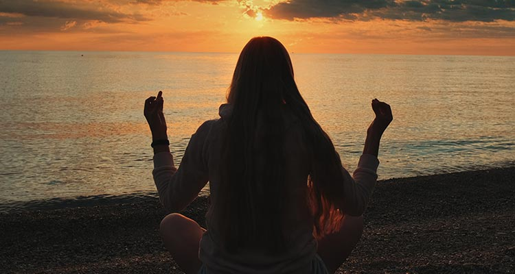 Back view of woman practicing yoga in meditation pose on the beach