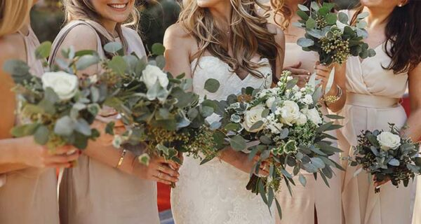 Bride and bridesmaids with pastel bouquets stand side by side