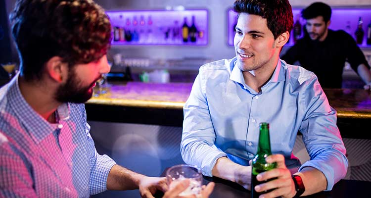 Friends interacting with each other at bar counter and having beer