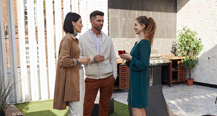 people chatting while standing at outdoor terrace during party