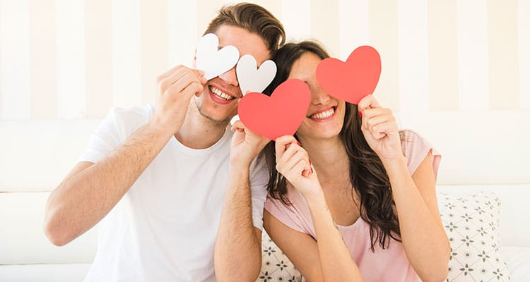 Happy couple posing with paper heart