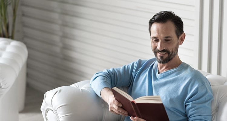 pleasant handsome happy man holding a book and reading it while sitting on the couch