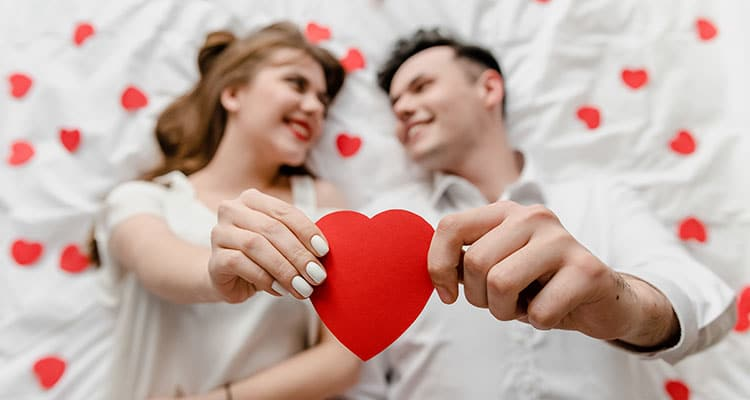 Man and woman in love in bed with heart shape