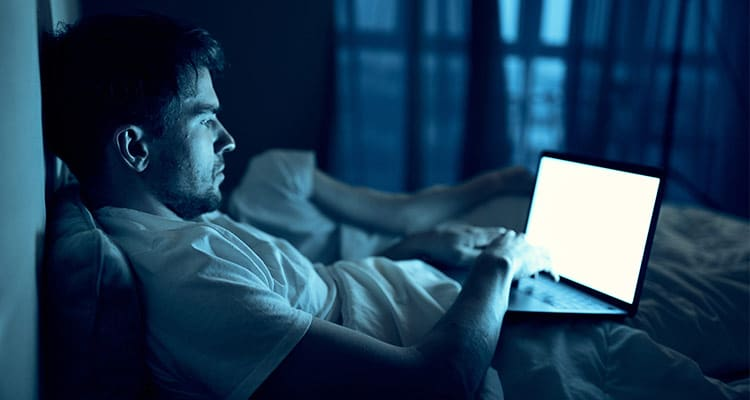A man works on a laptop in bed, a beloved woman sleeps