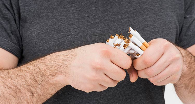 Mid section of a man breaking the cigarettes with hands