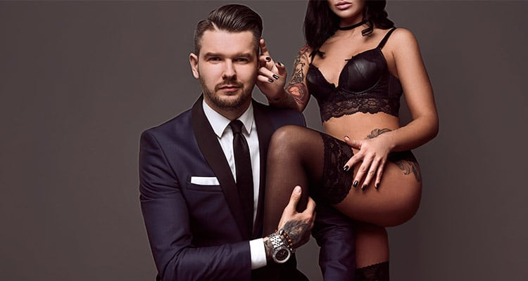 portrait brutal man elegant suit touches sexy girl with tattoo in ingerie