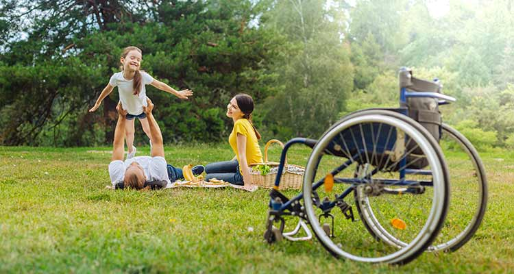 young man with disabilities lying on grass and lifting up his cheerful daughter as being an airplane while his wheelchair standing in the foreground