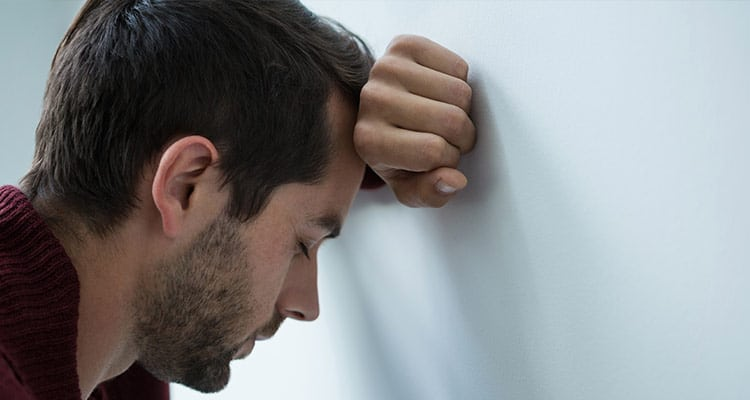 stressed-man-leaning-wall