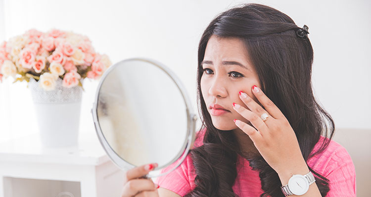 Woman holding a mirror and checking acne