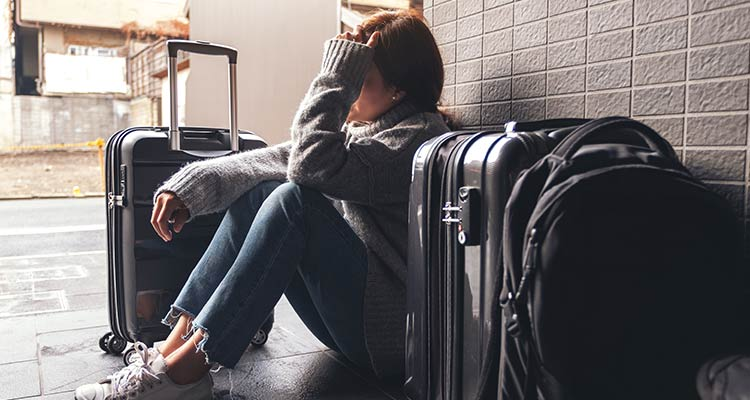 woman sitting with feeling sad with baggages