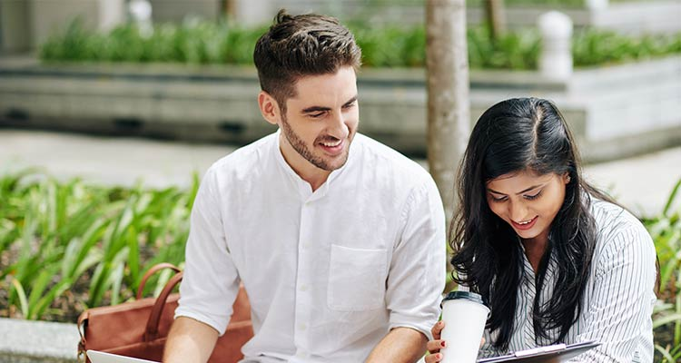 Young indian businesswoman showing report on clipboard to smiling colleague when they are sitting outdoors