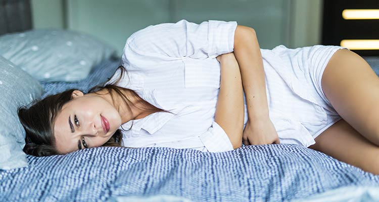 Young pretty woman in pain lying on bed