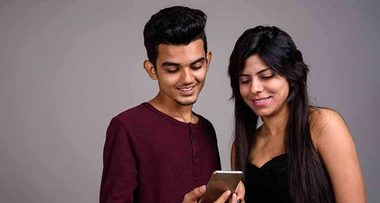Young Indian college friends checking out photo in phone