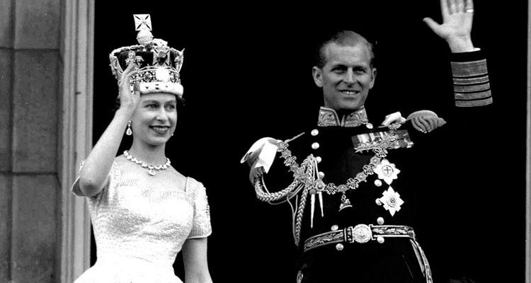 Prince Philip bent down before the queen during Elizabeth's coronation