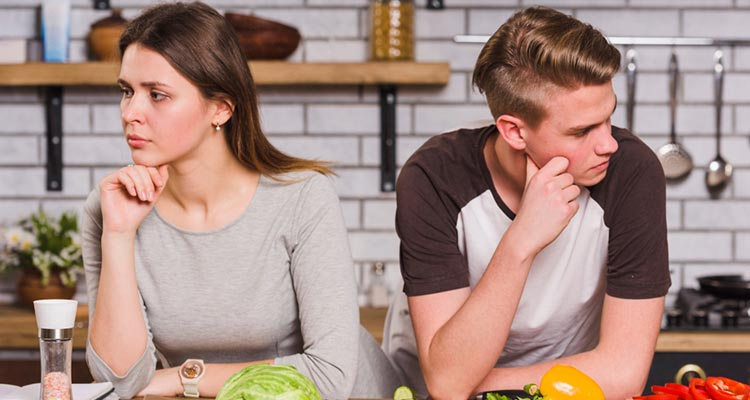 Upset young couple in quarrel in kitchen